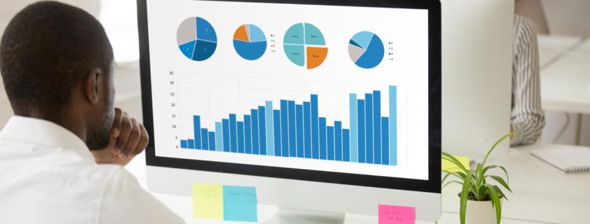 Black employee analyzing graphic data preparing statistical report on pc